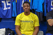 AFC Wimbledon defender Paul Kalambayi (30) wearing AFC Wimbledon foundation t shirt during the EFL Sky Bet League 1 match between AFC Wimbledon and Accrington Stanley at the Cherry Red Records Stadium, Kingston, England on 6 April 2019.