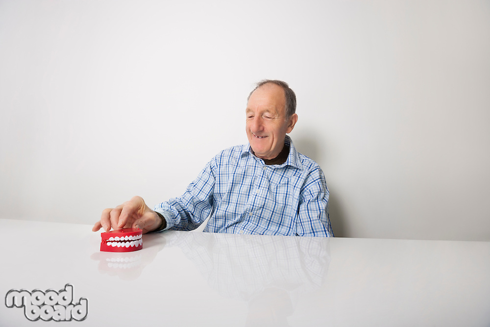 Happy senior man with dentures at table