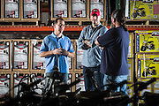 01/14/2016 134215 -- Garland, TX -- &copy; Copyright 2016 Mark C. Greenberg<br /> <br /> From left: President and COO Rick Sukkar and CEO Alex Keechleof talk with warehouse manager Kevin Sadler in the warehouse of Garland, Texas based Monster Moto