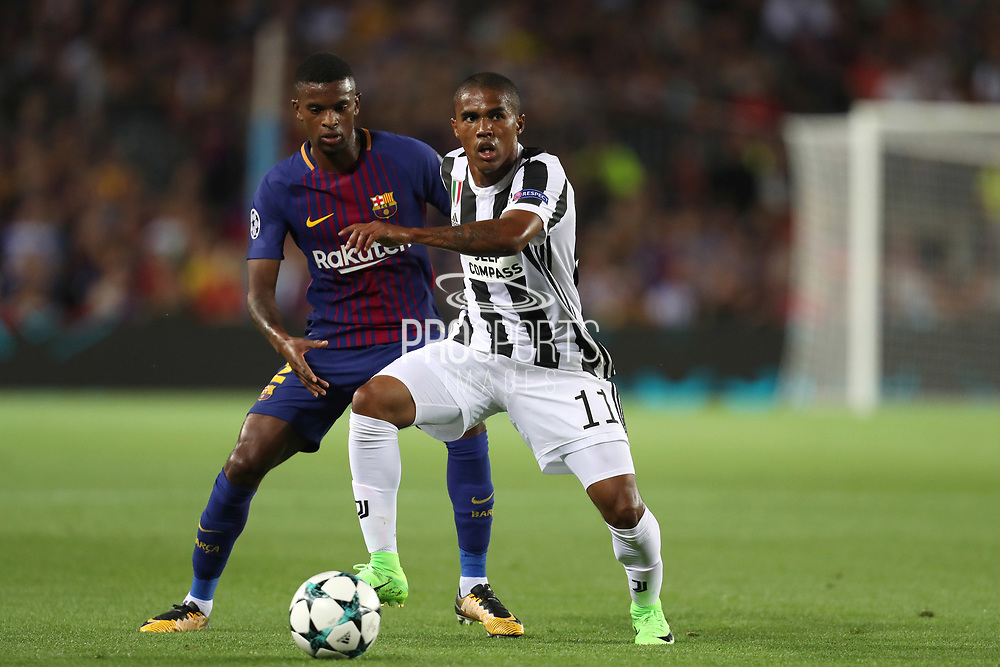 Douglas Costa of Juventus controls the ball under pressure from Nelson Semedo of FC Barcelona during the UEFA Champions League, Group D football match between FC Barcelona and Juventus FC on September 12, 2017 at Camp Nou stadium in Barcelona, Spain. Photo: Manuel Blondeau/AOP.Press/ProSportsImages / DPPI