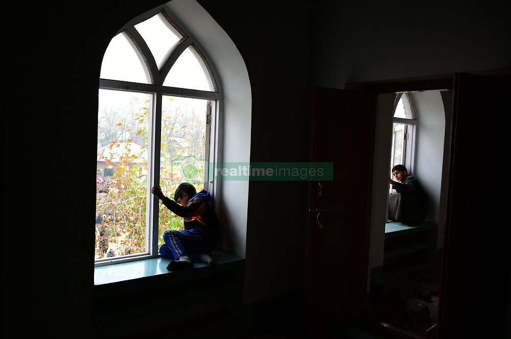 November 10, 2018 - Pulwama, Jammu and Kashmir, India - Kashmiri Muslim boys watch the funeral of the two rebels identified as Liyaqat Wani and Wajid ul Islam of Pulwama district of Indian Administered Kashmir on 10 November 2018. Two Hizb ul Mujahideen militants were killed in a gunfight with the government forces in Tikken area of south Kashmir's Pulwama district on Saturday, police said. (Credit Image: © Muzamil Mattoo/Pacific Press via ZUMA Wire)