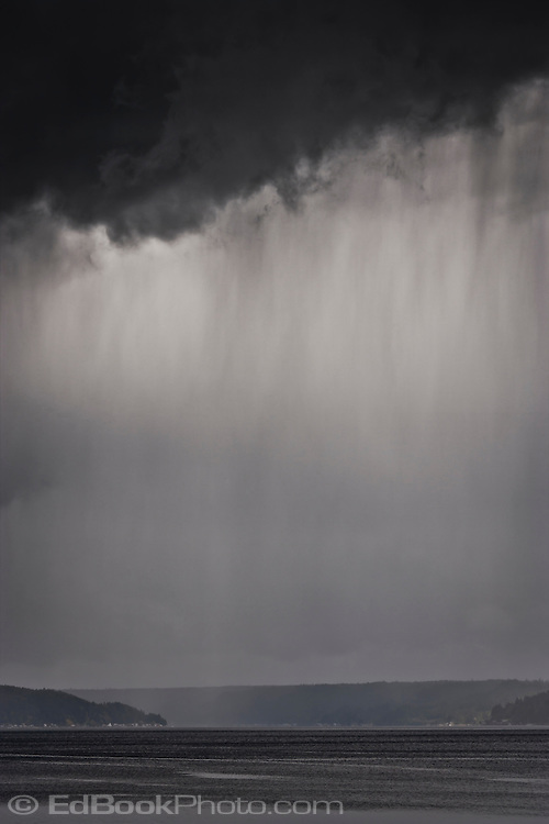 Rain streams from an omnious dark nimbus cloud over the Hood Canal of Puget Sound, Washington, USA