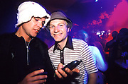 Two men in a club. One wearing a white hat, looking at a mobile phone. UK 2000