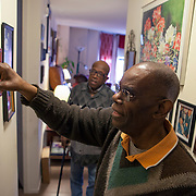 Mr. Johnson, background, and caretaker Mr. Griffin look at old photographs on the wall. John E. Johnson, who is not eligible for medicaid, receives services for 12 hours per week through Illinois&rsquo; Community Care Program. Johnson worries his services will be cut if the state transition seniors like him to a new program. The state employs Reggie Griffin to help Johnson with daily chores so he is able to stay in his home, as opposed to going to an nursing home. <br /> Photography by Jose More