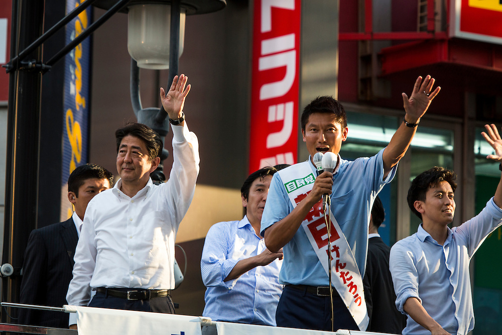 TOKYO, JAPAN - JULY 03 : Japanese Prime Minister Shinzo Abe (L), president of the ruling Liberal Democratic Party and Candidate Kentaro Asahi (R), greets the voters during the July 10 Upper House election campaign in Shibuya crossing, Tokyo prefecture, Japan, on July 3, 2016. Photo: Richard Atrero de Guzman