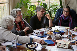 Ann Mintz and Dayle Friedman (center) discuss current topics in the news to write postcards and thank you notes about, during a meeting of activists at a West Mount Airy home, on Friday afternoon. (Bastiaan Slabbers for WHYY)