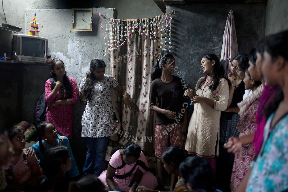 Mayuri Mahesh Pandit, 13, (right - next to the door) is participating to the Unicef-run 'Deepshikha Prerika' project inside the Milind Nagar Pipeline Area, an urban slum on the outskirts of Mumbai, Maharashtra, India, where she resides with her family.