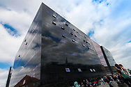 Event Photography images taken during the 2018 Podcast Day, held at The Black Diamond (Den Sorte Diamant) in Copenhagen, Denmark.  <br /> <br /> A close-up angled shot of the architecture of the Black Diamond building as attendees gather outside.  <br /> <br /> © Event Photographer in Copenhagen Matthew James
