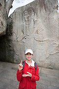 Songnisan National Park. Beopjusa Temple. Tourist mimicking relief of Buddha for souvenir shot.