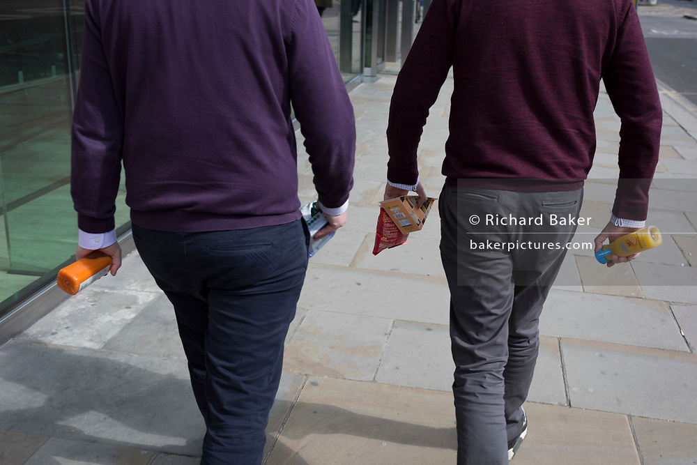 Two businessmen wearing informal jumpers take their lunches back to the office in the City of London, the capital's financial district, on 25th March 2019, in London, England.
