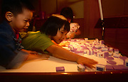 Children play with Mahjong tiles at a night-club, on 10th August 1994, in Macau, China. The Macau Special Administrative Region is one of the two special administrative regions of the People's Republic of China (PRC), along with Hong Kong. Administered by Portugal until 1999, it was the oldest European colony in China, dating back to the 16th century. The administrative power over Macau was transferred to the People's Republic of China (PRC) in 1999, 2 years after Hong Kong's own handover.