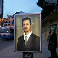 A Syrian woman walks past a picture of Syrian President Bashar Assad on a street in Aleppo, Syria. March 2006.