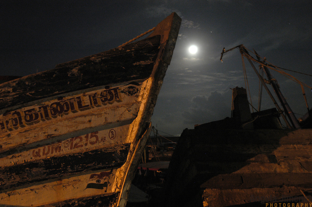 Destroyed fishing boats sit under a full moon in the fishing village of Nagapattinam in Tamil Nadu, India on January 24, 2005, after the area was struck by the Indian Ocean Tsunami on December 26, 2004. Generated by an earthquake on the ocean floor, the tsunami devastated the fishing industry along the southeastern coast of India.