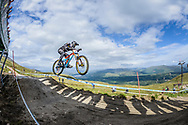 Dylan Levesque grabs some air whilst crowds watch from above at the top of the Fort WIlliam downhill track during Saturday practise at the UCI Mountain Bike World Cup.