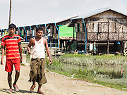 11 NOVEMBER 2014 - SITTWE, MYANMAR: People walk down the street in a Rakhine Buddhist IDP camp near Sittwe. About 700 Rakhine Buddhist families live in an Internal Displaced Persons (IDP) camp on the edge of Sittwe. The people in the camp lost their homes in Sittwe in 2012 when Buddhist mobs rioted and burnt down Rohingya Muslim homes and businesses. The Buddhists' homes were mistakenly destroyed by other Buddhists or intentionally destroyed by retaliating Muslims during the 2012 violence. Unlike the Muslims, who live in much larger camps further from Sittwe, the Buddhists are allowed to come and go into downtown Sittwe and their homes are built in the traditional style, on stilts with large windows, and so are much more comfortable.   PHOTO BY JACK KURTZ
