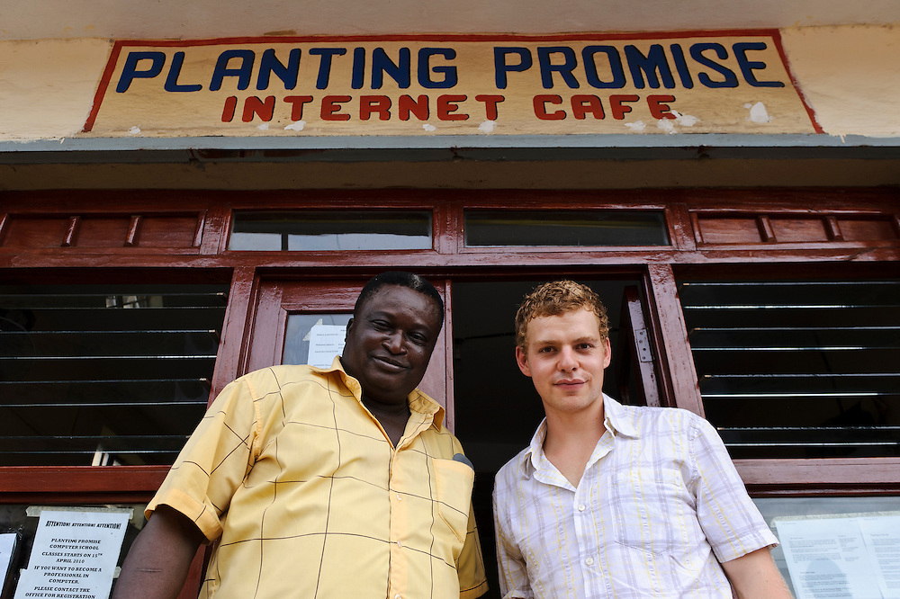 Rocco Falconer and Eddie Boston-Mammah of Planting Promise outside the charity's internet cafe, Freetown, Sierra Leone. Planting Promise is an organization dedicated to the development of education in Sierra Leone. Its aim is to bring opportunities to initiate self-run, self-supporting projects that offer real solutions to the difficulties facing the world's poorest country. They believe real and lasting development comes from below, from local projects that address specific needs, rather than large international models. To this end, they currently run five projects that aim to bring wealth into the country through business. The profits from these businesses are then used to support free education for children and adults...Through the combination of business with social progress, the charity hopes that they are providing real, lasting and profound changes for the better, by promoting sustainable and beneficial industry in the country, and putting it to the service to the needs of the people. As well as providing the income to fund the school, the farms will also be an example of successful commercial enterprise to teach the children in the school the viability of profit-making schemes that go beyond subsistence models, the only things the children of these desperately poor areas are accustomed to. By learning particular details of the challenges that they will face, the children will emerge from this school equipped to contribute in a real way to their society.