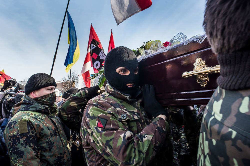 KIEV, UKRAINE - JANUARY 26: Men carry a casket containing the body of Mikhail Zhiznevsky, 25, an anti-government protester who was killed in clashes with police, after a memorial service in his honor on January 26, 2014 in Kiev, Ukraine. After two months of primarily peaceful anti-government protests in the city center, new laws meant to end the protest movement have sparked violent clashes in recent days. (Photo by Brendan Hoffman/Getty Images)