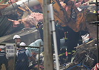 A dead body is removed from the rubble of the CTV building in Christchurch City Centre after a Powerful earth quack ripped through Christchurch, New Zealand on Tuesday lunch time killing at least 65 people as it brought down buildings, buckled roads and damaged churches and the Cities Cathedral. Photo Tim Clayton