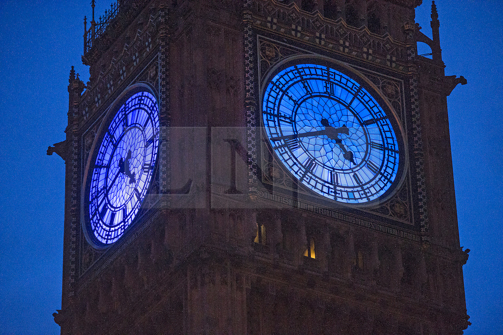 © London News Pictures. 31/12/2015. London, UK.  Big Ben lit up blue ahead of the 2016 New Year celebrations this evening December 31, 2015 in London, England. This year Big Ben is lit blue as  part of the Unicef New Year's Resolution for Children, who are sponsoring the event. Photo credit: Ben Cawthra/LNP