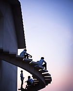 Boys line an outside staircase in Vietnam watching the sunset.