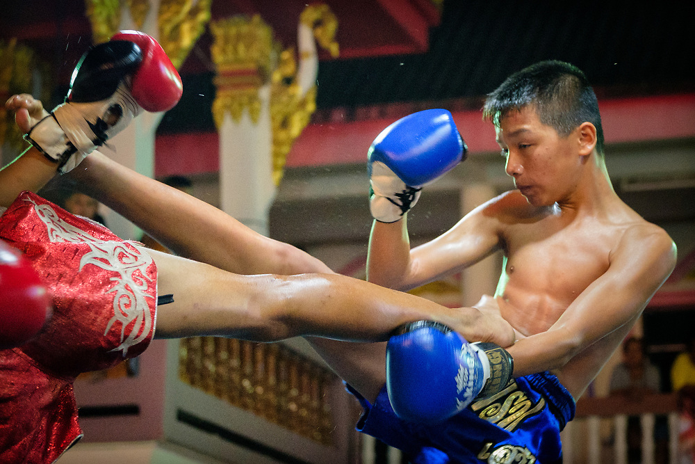 A young Muay Thai fighter lands a side kick during a boxing match at a festival in Nakhon Nayok Thailand, Jan 30, 2018.