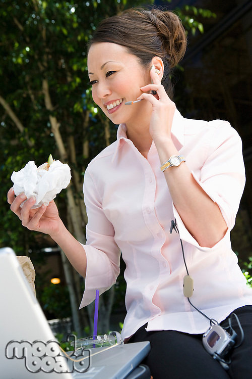 Young woman using mobile while eating sandwich