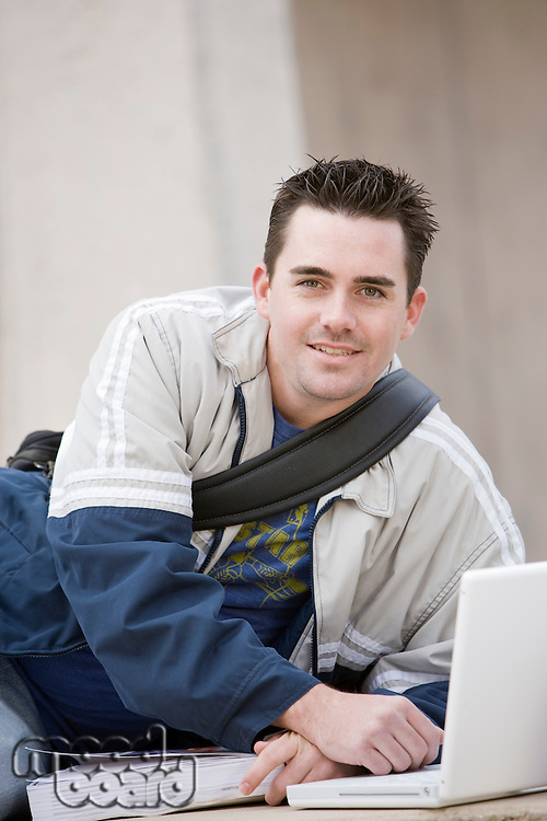 Young man with laptop and book