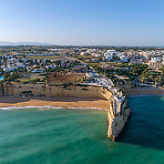 Aerial rocky famous seascape cape and Senhora da Rocha church on top of the cliff, in Algarve south coast, Portugal.