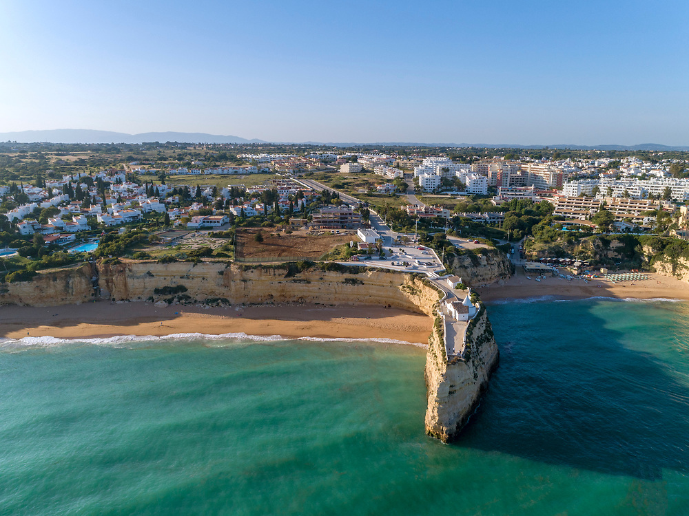 Aerial rocky famous seascape cape and Senhora da Rocha church on top of the cliff, in Algarve south coast, Portugal.