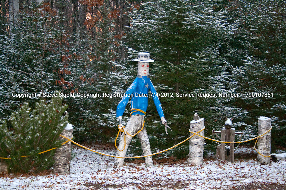 Outdoor snowy birch tree sculpture of cowboy carrying a lasso and wearing a star badge. Cable Wisconsin WI USA