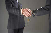 Businessmen shaking hands wrapped in gold chain with padlock mid section