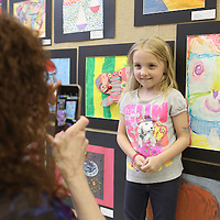 "Adam Robison | BUY AT PHOTOS.DJOURNAL.COM<br /> Emily Ard, a Kindergarten student at Parkway Elementary School, has her picture taken by her mother Susan, as she stands by her art work ""Paul Klee Cat"" during the Tupelo Public School District Art Show at the Gum Tree Museum of Art Thursday afternoon."