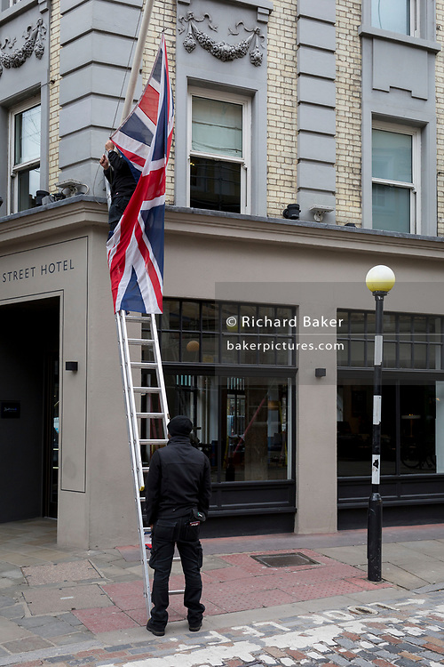 As a workman holds the bottom of ladders, a British Union Jack flag is hoisted by a worker outside a West End hotel located on the corner of Monmouth Street in Soho, on 3rd March 2020, in London, England.