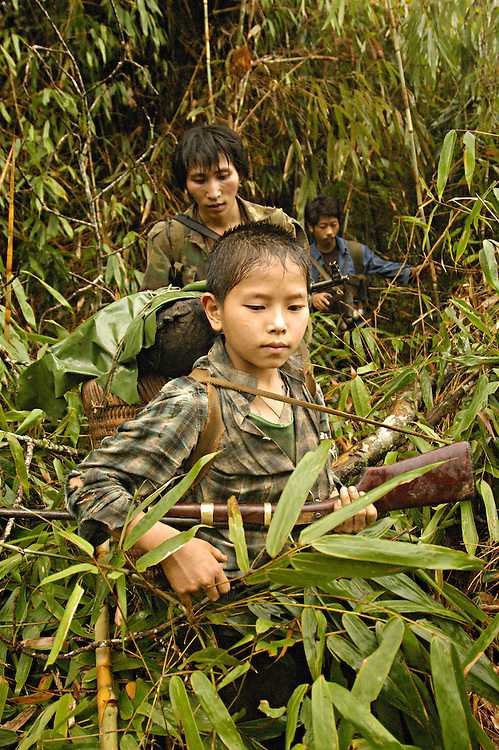 Hua Li and Hmong soldiers cut through the jungle on their way to the site of the April 6th massacre, near Vang Vieng, Laos, June 30, 2006...**EXCLUSIVE, no tabloids without permission**  .Pictured are a group of Hmong people who report an attack against them April 6, 2006 by Lao and Vietnamese military forces.  26 people perished, 5 were injured, and 5 babies died shortly after because their dead mothers could not breast-feed them.  Only one adult male was killed, the other 25 victims were women and children (17 children).  The Lao Spokesman for the Ministry of Foreign Affairs says this is a fabrication, an investigation has been completed, and there was no attack.  The Hmong group says no officials have interviewed witnesses or visited the crime scene, a point the Lao Spokesman did not deny.  ..The Hmong people pictured have hidden in remote mountains of Laos for more than 30 years, afraid to come out.  At least 12,000 are said to exist, with little food, scavenging in the jungle. Most have not seen the modern world.  The CIA trained and funded many Hmong hill tribes in Laos from 1961 to 1973 to fight communism.  The Hmong suffered massive casualties defending their homeland and rescuing US pilots.  When America withdrew from the conflict most Hmong were left alone to face the might of the North Vietnamese Army.  The Royal Lao Government fell to the communists and the Hmong became outcasts in the country they fought to defend.  Since 1975, under the communists, thousands of reports evidence the Hmong have suffered frequent persecution, torture, mass executions, imprisonment, and possible chemical weapons attacks.  Reports of these atrocities continue to this day.  The Lao Government generally denies the jungle people exist or that any of this is happening.  The Hmong group leader, Blia Shoua Her, says they are not part of the Hmong resistance and want peace.  He claims they are just civilians defending their families, hoping to surrender to the UN....