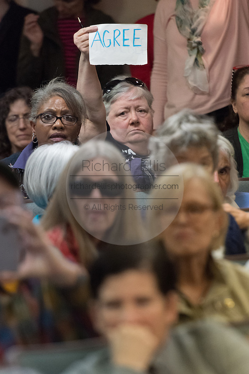 "A member of the audience holds up a sign with the word ""Disagree"" during a heated discussion with U.S. Sen. Tim Scott and U.S. Rep. Mark Sanford at a town hall meeting February 18, 2017 in Mount Pleasant, South Carolina. Hundreds of concerned residents turned up for the meeting to address their opposition to President Donald Trump during a vocal meeting held by U.S. Rep. Mark Sanford and Senator Tim Scott."
