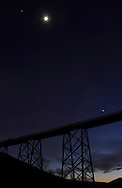 Salisbury Mills, New York  - The planet Jupiter, top left, the moon and the planet Venus, lower right, share the twilight sky above the Moodna Viaduct railroad trestle  on Jan. 29, 2012.