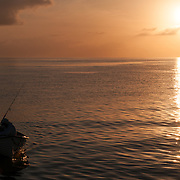 A small boat with fisherman comes in at the end of the day, silhouetted against the setting sun on a calm day on the Great Barrier Reef, Queensland, Australia.