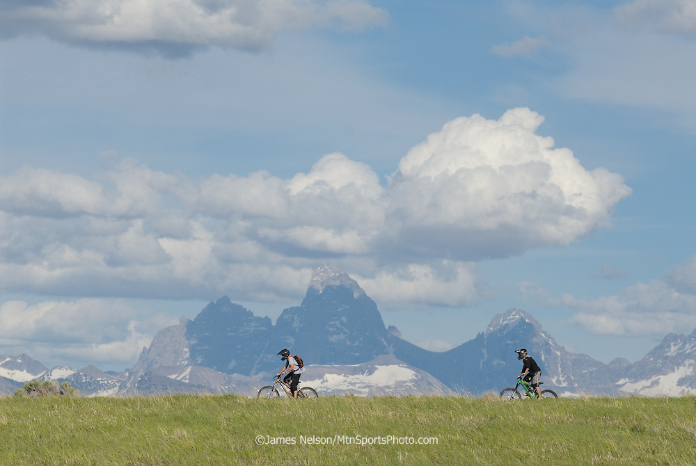Mountain bikers ride a ridgeline in the Big Hole Range of eastern Idaho, with the Teton Range of western Wyoming in the background.