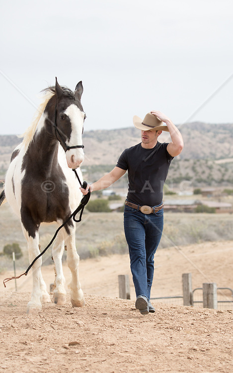cowboy walking with a painted horse on a ranch
