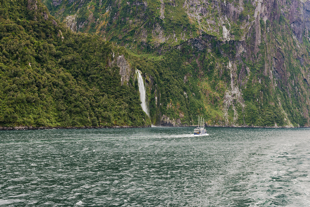 A tourboat sailing in Milford Sound goes past a waterfall on the side of the mountain.