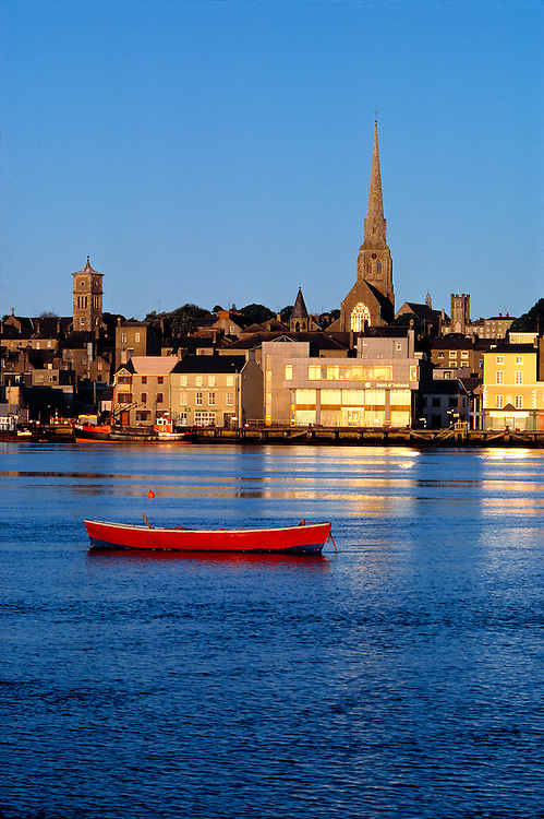 Late light over Wexford Harbor illuminates the windows of buildings on shore, in County Wexford, Ireland.
