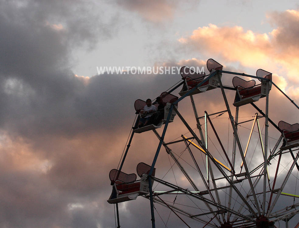 Middletown, N.Y. - People riding on a ferris wheel at a carnival are silhouetted against the clouds at twilight on May 20, 2006.