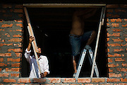 2016/10/10 – Bahia de de Caráquez, Ecuador: A son helps his father to rebuild a window of their home in Bahia de Caráquez, Ecuador, 10th October 2016. Many people don't believe they will get any Government help, so they have started to rebuild their houses by themselves. (Eduardo Leal)