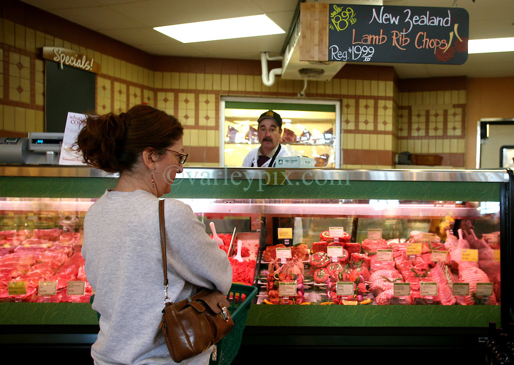 01 Feb 2006. Uptown, New Orleans, Louisiana.  Post Katrina. <br /> The Whole Foods supermarket reopens amidst great celebration 5 months after  the city was hit by Hurricane Katrina.A shopper browses the meat display.<br /> Photo; Charlie Varley/varleypix.com