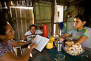 Solange Da Silva Correia reads the Bible to her husband and daughter-in-law at breakfast prayer time in her riverside home near the town of Caviana, Amazonas, Brazil. (Solange Da Silva Correia is featured in the book What I Eat: Around the World in 80 Diets.) PJM