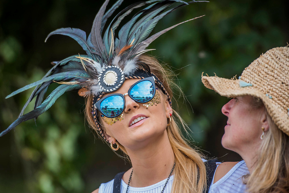 A womanin a feathered head-dress, and her mother enjoy the Yoga class on the waterfront stage - The 2016 Latitude Festival, Henham Park, Suffolk.
