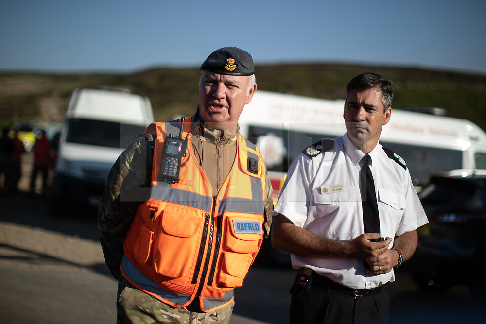 """© Licensed to London News Pictures . 28/06/2018 . Saddleworth , UK . Wing Commander GARY LANE Lane (l), RAF Regional Liaison Officer for the North West and Area Manager TONY HUNTER of Greater Manchester Fire and Rescue host a press conference at Higher Swineshaw Reservoir . The army are being called in to support fire-fighters , who continue to work to contain large wildfires spreading across Saddleworth Moor and affecting people across Manchester and surrounding towns . Very high temperatures , winds and dry peat are hampering efforts to contain the fire , described as """" unprecedented """" by police and reported to be the largest in living memory . Photo credit: Joel Goodman/LNP"""
