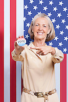 Portrait of senior woman pointing at election badge against American flag