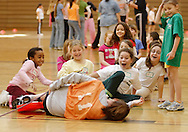 Middletown, N.Y. - A group of 7-year-old girls react as one of their leaders fall over during a game at National Women in Sports Day on Feb. 11, 2006. Orange County Community College's Department of Movement Science celebrated the 20th Anniversary of National Girls and Women in Sports Day by holding an event for young girls that included volleyball, basketball, soccer, games and swimming.