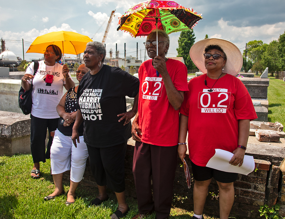 "Janice Dickerson, Vivian Ann Craig Chiphe, Robert Taylor and his daughter, Tish Taylor, in the Reveille Town Cemetery. with  members of CADA and supporters at the Reveille Town Cemetery in Plaquemine, Louisiana on the fourth day of the Coalition Against Death Alley's 5 day march. The Coalition Against Death Alley (CADA), is a group of Louisiana-based residents and members of various local and state organizations, is calling for a stop to the construction of new petrochemical plants and the passing of stricter regulations on existing industry in the area that include the groups RISE St. James, Justice and Beyond, the Louisiana Bucket Brigade, 350 New Orleans, and the Concerned Citizens of St. John.  Louisiana's Cancer Alley, an 80-mile stretch along the Mississippi River, is also known as the ""Petrochemical Corridor,"" where there are over 100 petrochemical plants and refineries. The cemetery is located within the fenceline of Westlake Chemical plant that controls acess to it."